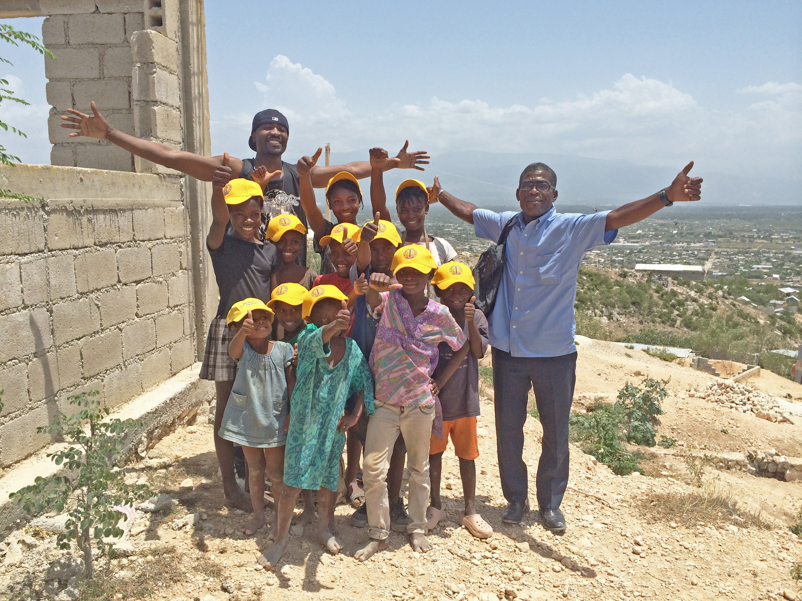Volunteers and Haitian Kids with arms stretched out